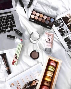 Favourites on a flatlay: eyeshadow palette, On Top by Anna Nooshin, macarons, lipstick, my macbook.