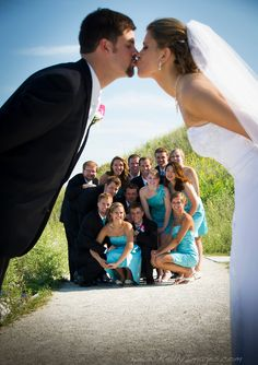 Bride and groom kissing while wedding party look on.