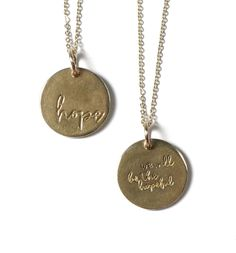 """Double sided 3/4"""" circle pendant hand carved and cast in bronze with an 18"""" brass yellow-gold plated flat cable chain.  Side A: """"hope"""" Side B: """"we will be the hopeful""""   Pendant is hand carved, cast and assembled in the USA. Packaged in small gift tin case with clear top."""