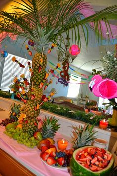 Pineapple Palm at my daughter's 10th. I made a metal frame from a piece of sheet metal. Welded on a very thin pipe and simply slid the pineapples down onto it. Stuck some palm leaves from the yard on top and done!