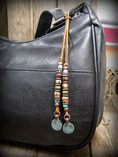 A new design I created for purse charms....beaded suede leather with various boho style beads and a mykono patina spiral charm dangles on each end. This tassel is unique....you wrap it around a purse strap with a loop. You can add this to a purse, bag or belt loop on jeans really looks cool too! Add it to anything you can loop it around for a boho native accessory thats like adding a piece of jewelry! Create your own fashion using something unique .... an accessory for some extra needed…