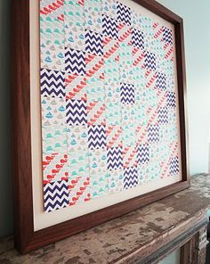 Paper Quilt!  Use scrapbook paper, cut into squares, arrange, frame.  So clever!