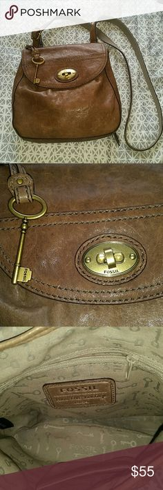 """Fossil crossbody leather bag Gorgeous muted brown leather purse. Includes iconic fossil keychain. Front features flap secured closure, interior is in mint condition and has a zippered pocket and cell phone pocket. Back features zippered wallet pocket with ID holder. Rustic leather is in excellent condition with only one light spot of discoloration on the back (barely noticeable in photo) from rubbing on new jeans.  Measures 10"""" ? 9"""" ? 2"""", strap adjustable up to 46"""" and his perfectly at hip…"""