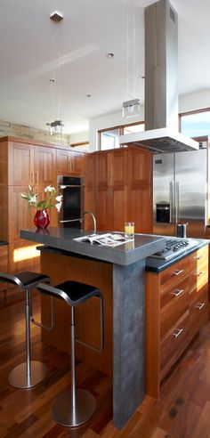 Kitchen - Modern kitchen with natural woods, stone and shiny surfaces.