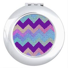 A sweet compact mirror with a colorful chevron pattern in yellow, green, blue, purple, pink and orange displayed as a tiled mosaic. Design has a textured snakeskin appearance.