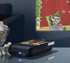 """iPhone Pocket Projector:  """"This tiny device docks onto your iPhone 4 and is able to project video and images up to 50"""" on a wall, ceiling or any other flat surface using a super-bright 15-lumen LED projector lamp. It features focus adjustment, integrated 0.5W speakers and a built-in rechargeable battery that doubles as a back-up battery for your iPhone. It's perfect for travelers, businesses, kids, or just anyone who wants to share photos and videos with family and friends."""""""