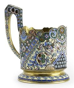 A Russian silver-gilt and cloisonné enamel tea-glass holder <br  /> maker's mark of Konstantin Skvortsov, Moscow, 1908-1917 <br  /> decorated with stylized polychrome floral scrolling with panels enclosing geometrical motifs, the flared foot with geometric scrolling, the angular handle similarly decorated, shaped rim <br  /> 12cm maximum height, 7.5cm diameter <br  /> Provenance: <br  /> Christie's New York, The Greenfield Collection of Russian Enamels, 20th October 1998, lot 227