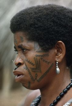 Africa | Makonde woman wears a lip plug with nail and many facial tattoos. Mozambique. | ©Volkmar K Wentzel