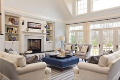 pale blue living room with white trim, blue square ottoman, striped rug (Sherwin Williams, Cotton White)
