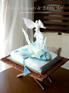 The Prayer Book - open book cake with handmade dove in flight | Fancy Favours & Edible Art -- #dove #bird #waferpaper #sculpted #topper #3d #gravitydefying #cake #prayer #book#bookcake #noveltycake #carvedeffect #blue #white #beads #rosary #chocolate #fondant #cakedecorating