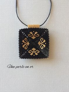 3D square pendant with arabesque patterns / black and gold miyuki pearls / on waxed cord / peyote weave