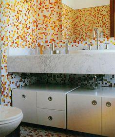 A ideia deste projeto é criar um ambiente divertido. O mosaico de cores é equilibrado pelo branco, que dá clareza ao banheiro. Os móveis alongados esticam o espaço, e guardam o excesso de objetos, sem carregar o ambiente. Os créditos vão para o arquiteto David Bastos.