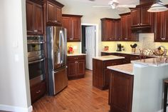 These dark wood cabinets by @showplacecab lend such a rich look to this kitchen! With granite countertops, stainless steel appliances, double wall ovens and a kitchen island, this space is super functional and beautiful!!  All this and more available from Adalay Interiors in Tampa Bay! www.adalay.com