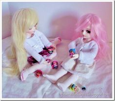 """Two ball jointed dolls playing with their """"dolls""""."""