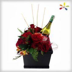 VINO ROSE Diseño compuesto por una botella de vino con rosas, astromelias y follaje fino en caja de madera color chocolate
