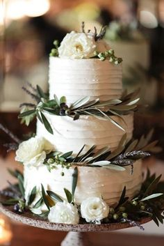 Tuscany inspired tiered cake decorate with olive leaves.