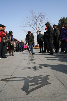 A man writes with water on a place in Xian... Photo by Ole Wåhlin