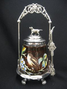 "Victorian Pickle Castor,  enameled bird & floral on amberina coinspot glass insert, fancy footed silverplate holder and tongs, figural dog finial, signed New Haven, excellent, 10"" tall. Sold for $600 in 2012"