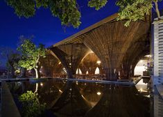 Waterside cafe at the Kontum Indochine Hotel in Vietnam designed by Vo Trong Nghia Architects and filled with conical bamboo columns.