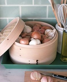 Bamboo steamer used as storage for onions and garlic.