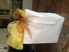 White gift bag, light yellow paper, plastic pearls I used to wear as a kid (!), wired bronze organza ribbon, and three sprigs of rosemary. Gifting a batch of homemade granola and wanted something prettier than a plastic bag.