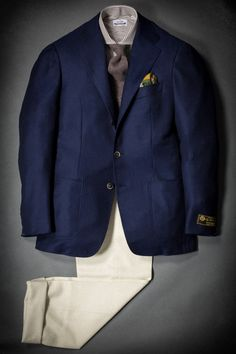 Navy jacket, white shirt with brown dress stripes, brown tie, khakis