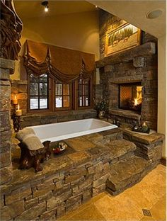 It can`t get more rustic then this bathtub base with it`s rock facade, steps built out of stones and roaring fireplace. I half expect to see a grizzly bear peaking in the window.