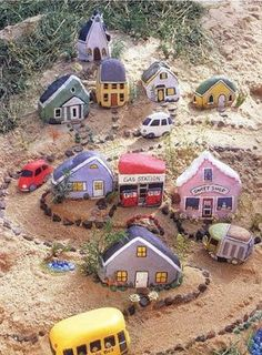 Painted village out of rocks and bricks. I so need this in my garden for my grandson.