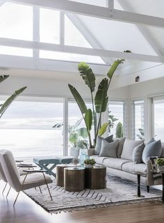 A home need not be rife with anchors, shells, and maritime flags to have a soothing, coastal feel. Let me introduce you to my ideal modern beach house. Drawing a palette from sand, sky and sea…More Coastal Living Rooms, Living Room Decor, Beach Living Room, Living Area, Cottage Living, Tropical Living Rooms, Plants In Living Room, Hamptons Living Room, High Ceiling Living Room