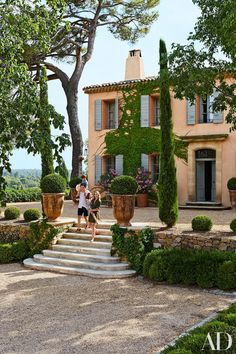 Frédéric Fekkai's Gorgeous Vacation Home in the South of France Photos | Architectural Digest. Fekkai and Von Wulffen with their children Philip and Cecilia on the entrance-court steps, which are flanked by boxwood in monumental Anduze pots. The house's façade features a traditional Provençal ocher finish and gray shutters.