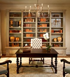 Bookcase with burnt orange books, rust boxes and ocher confit pots -- Thompson Custom Homes