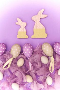 two wooden bunnies and easter eggs on purple background