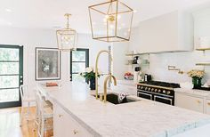 """While they couldn't save the home's original brass hardware, it inspired the new kitchen's hardware. As for the ceiling fixtures, they went big.""""With lighting, nothing is more important than scale. Tiny pendants over a kitchen island kill me,"""" says Gen."""
