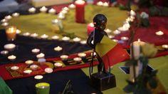 Eine Miniaturskulptur von Manneken Pis hält die belgische Flagge. Am Place de la Bourse (Beursplein) in Brüssel trauern  die Menschen.
