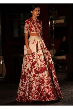 Model walking the ramp with red and white floral gown for sabyasachi collection of Indian couture week July 2014