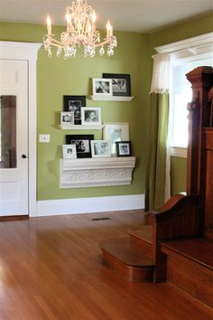 The green paint is Behr, Salted Ash. I love the staircase, the floors and the shelves, as well as the door and chandelier. The whole entry is just so pretty and welcoming.