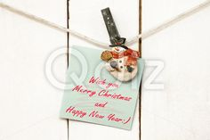 Qdiz Stock Photos | Christmas snowman clothespins holding greeting note paper,  #background #card #Christmas #closeup #clothesline #clothespin #decoration #decorative #eve #figure #fun #funny #green #greeting #hanging #holding #holiday #light #little #Merry #new #note #object #paper #pin #postcard #rope #small #snowman #toy #traditional #white #wood #wooden #xmas #year