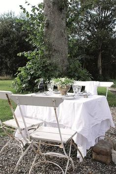 Party hack we love: Instead of dining directly on your outdoor table's rusty or wooden surface, cover it with a white linen sheet.