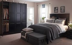 A large bedroom with a black bed and bedside tables. Shown together with a large black wardrobe combination and two footstools with grey cover.