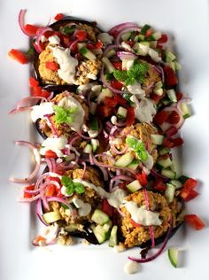 Grilled Eggplant Topped with a Chickpea Mash Tomato Cucumber Onion Relish, Tahini Sauce, Mint Garnish