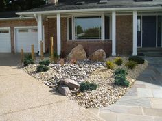 A triangular plot between the driveway and front walkway is decorated with rock, gravel and ornamental shrubs. Four bamboo canes, each smaller than the one before it, adds Asian flair to the hardscape.