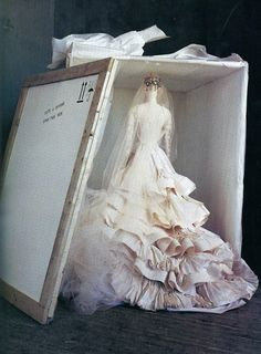 When shipped abroad, a Christian Lacroix wedding dress travels upright in a cloth case, each layer resting in a bed of tissue...
