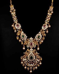 Stunning gold neckla Stunning gold necklace studded with kundan rubies and emeralds. Necklace with south sea pearl hangings.