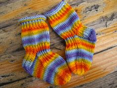Rainbow stripes--and a design that won't fall of baby feet! Baby-Socks pattern by Socks Street on Ravelry.