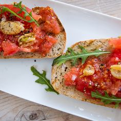 Pa amb tomàquet  4 UNPEELED GARLIC CLOVES - OLIVE OIL - 2 RIPE VINE TOMATOES - 2 THICK SLICES OF BREAD - SEVERAL ROCKET LEAVES - 1 TBS EXTRA VIRGIN OLIVE OIL - SEA SALT - BLACK PEPPER