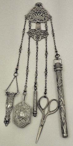 A Victorian silver four division chatelaine with embossed and scrolled ornament, Birmingham 1899, by Henry Matthews, hung with original etui (incomplete) and silver mounted ivory note pad, and now hung with Edward VII silver cylindrical bodkin case of Art Nouveau design, 6.25ins overall, London 1901, by Mordan & Co (damaged), a silvery metal propelling pencil by S. Mordan & Co, and a pair of stainless steel scissors Victorian Jewelry, Antique Jewelry, Antique Silver, Vintage Jewelry, Vintage Items, Antique Tools, Vintage Sewing Notions, Vintage Sewing Machines, Victorian Women