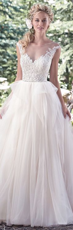 Our Dress Of The Week... Raeleigh by Maggie Sottero! The pinnacle of romance is found in this ball gown wedding dress. A stunning lace bodice, accented with Swarovski crystals and pearls, gives way to a whimsical tulle skirt, while illusion lace cap-sleeves dust the shoulder, and fall into a plunging illusion V-back.