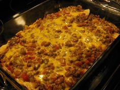 Easy Mexican Casserole 1 lb ground beef 1 can Ranch Style beans 1 10-12 ounce bag tortilla chips, crushed 1 can Ro-tel tomatoes 1 small onion, chopped 2 cups shredded cheddar cheese, divided 1 pkg taco seasoning 1 can cream of chicken soup 1/2 cup water sour cream and salsa for serving (directions in comments)
