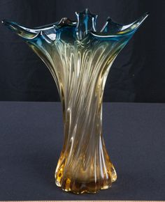 FLARED FROM THE TOP OUT, AND NARROWING TOWARDS THE BOTTOM, THIS LOVELY AMBER AND TURQUIOSE VASE WILL ADD SOME GLAMMER TO YOUR HOME. MEASURES 9 X 12. AS A MINOR CHIP AT TOP OF VASE.