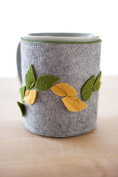 Coffee mug cozy AND mug - leaves -- needs to be cut lower to make room for drinking.(Note the simple way the felt leaves are attached) Mug Cozy, Coffee Cozy, Coffee Mugs, Felt Diy, Felt Crafts, Sewing Crafts, Sewing Projects, Christmas Craft Fair, Gift Wraping
